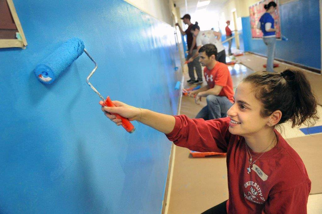 Woman in a red shirt painting a blue wall