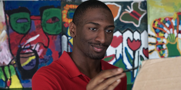 Image is of a black man named Naieer, wearing a red polo shirt and holding a paint brush. The background looks like an abstract painting.