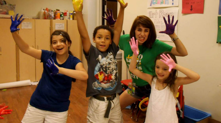 Image is of three kids and one staff members smiling for the camera and holding up their hands, which are covered in paint.