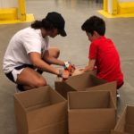 Image is of two kids on the floor with cardboard boxes