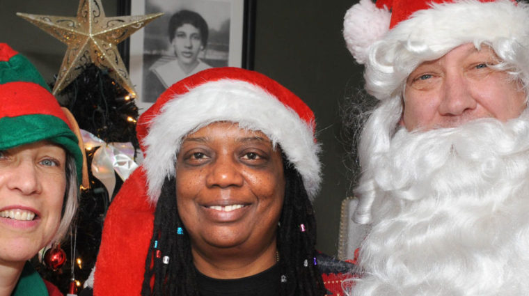 Image is of three people: the woman on the left is dressed as a Christmas elf and holding a candy cane, the woman in the middle is wearing a festive sweater and a Santa hat, and Santa is on the right!