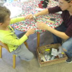 N used a hammer with a teacher's help to poke holes in his metal can lid wheels for his axel.