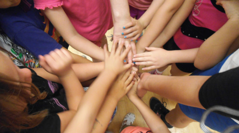 Image is of several children's hands coming together