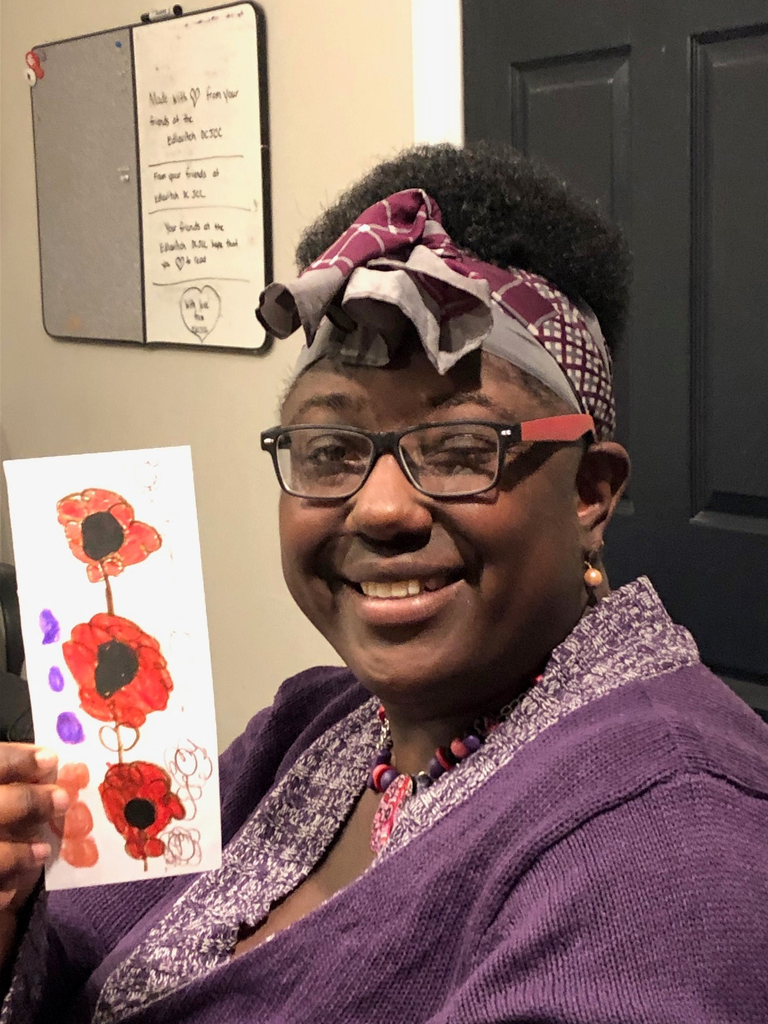 Image is of a smiling woman wearing a purple sweater and a grey/purple scarf around her wear. She is holding up a bookmark that is decorated with red and pink flowers.