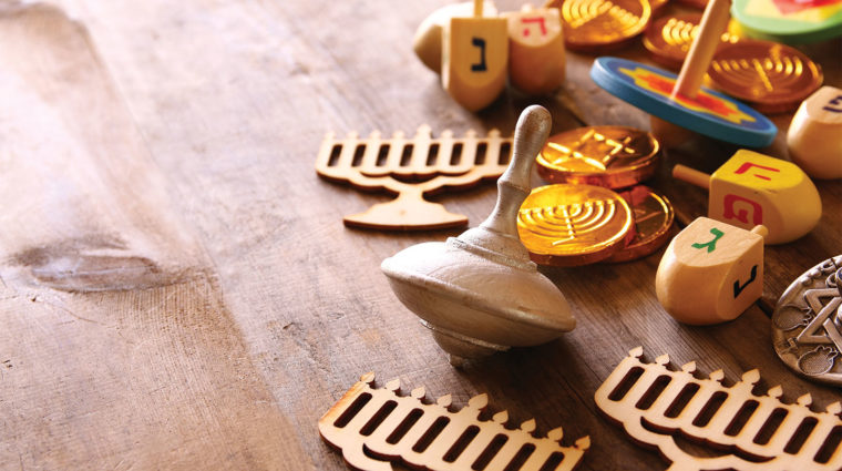 Image is of dreidels, wooden cutouts of menorahs, and gelt on a wooden background