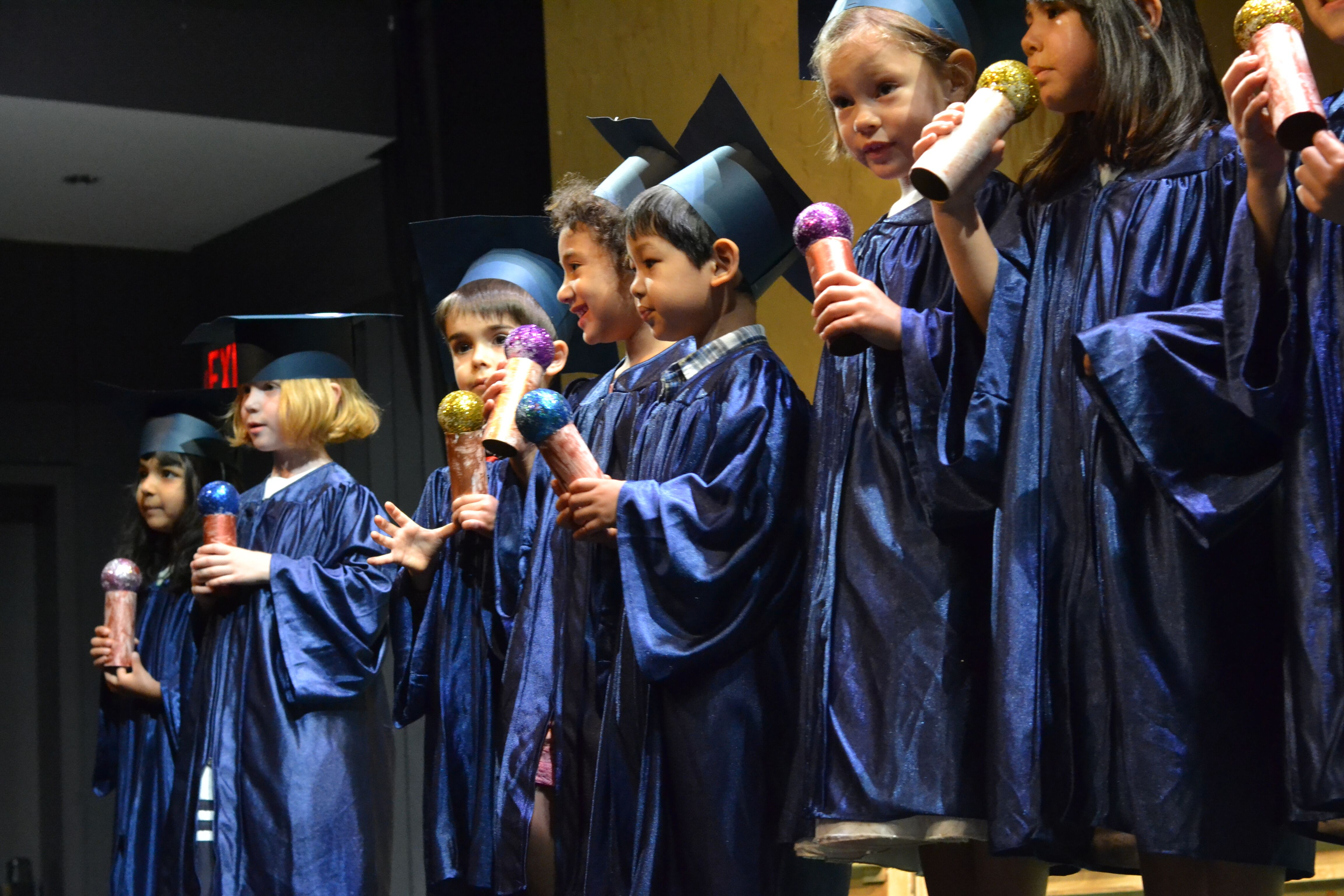 Image of children in blue caps and gowns at their preschool graduation ceremony